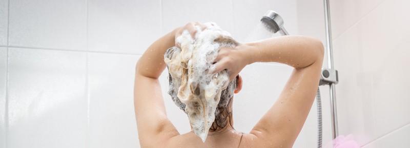 Die Frau verwendet antistatisches Shampoo.
