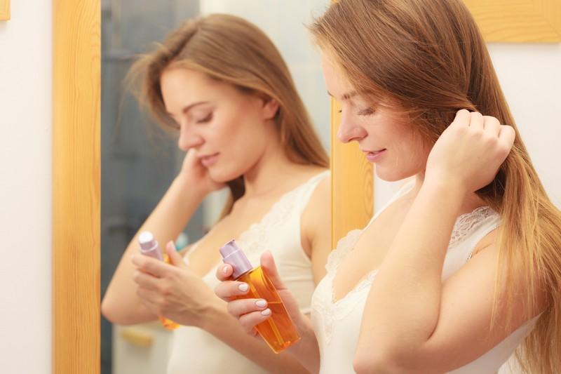 Die Frau verwendet Haaröl um keine elektrischen Haare zu haben.