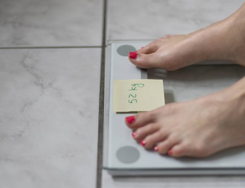Eine Frau findet einen Zettel auf ihrer Waage