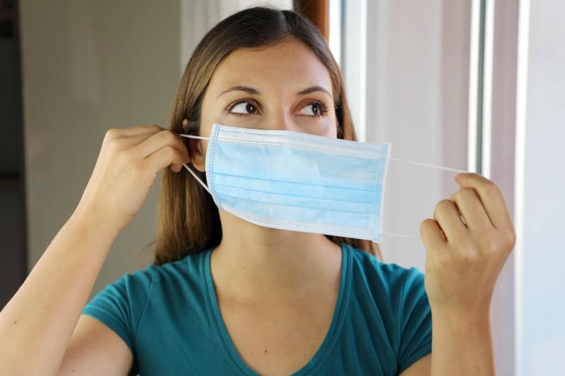 Das Foto zeigt eine Frau, die ihre Maske zum Lüften abnimmt, damit keine Pickel entstehen
