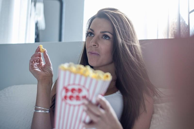 Frau isst während ihrer Periode Süßes.