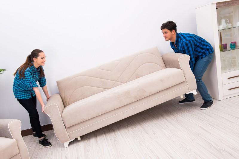 Eine Frau und ein Mann, die Möbel umstellen, damit die Wohnung schöner aussieht
