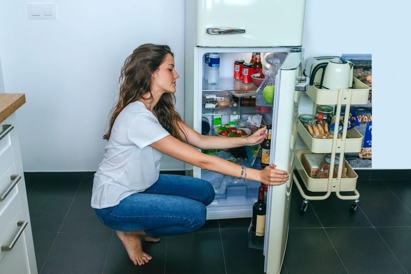 Junge Frau sitzt vor einem Kühlschrank mit Essen